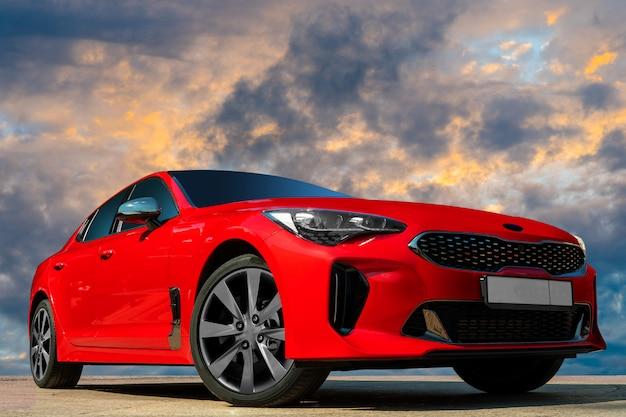Czerwony Samochód Na Tle Wieczornego Nieba. Premium Zdjęcia