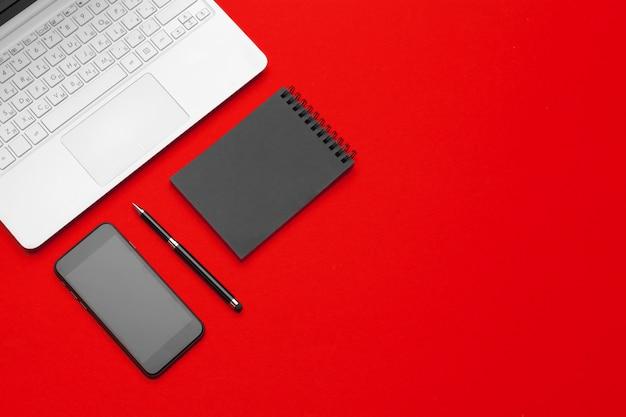 Czerwony stół biurkowy z artykułami biurowymi i materiałami biurowymi Premium Zdjęcia