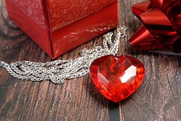 Czerwony Wisiorek Jako Serce I Pudełko Na Drewniane Tła Premium Zdjęcia