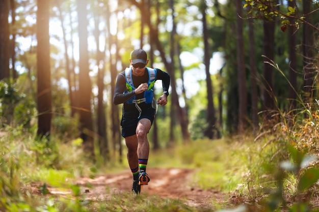 Człowiek biegacz szlaku. i stopy sportowca w sportowych butach do biegania po lesie Premium Zdjęcia