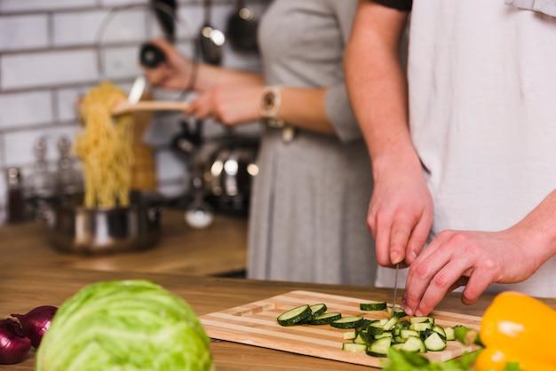Człowiek cięcia ogórków i kobieta gotowania makaronu Darmowe Zdjęcia