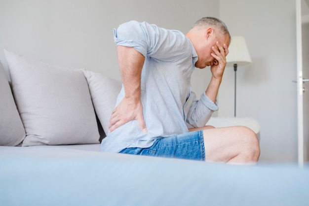 Człowiek cierpi na ból pleców w domu Premium Zdjęcia