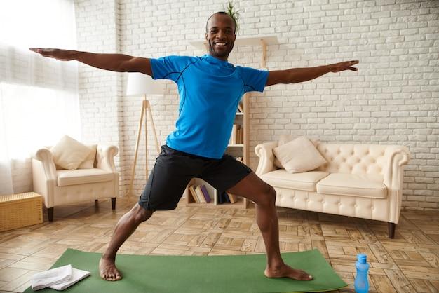 Człowiek ćwiczy zaawansowaną jogę w domu Premium Zdjęcia
