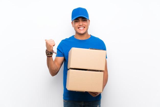 Człowiek dostawy na pojedyncze białej ścianie, wskazując na bok, aby przedstawić produkt Premium Zdjęcia