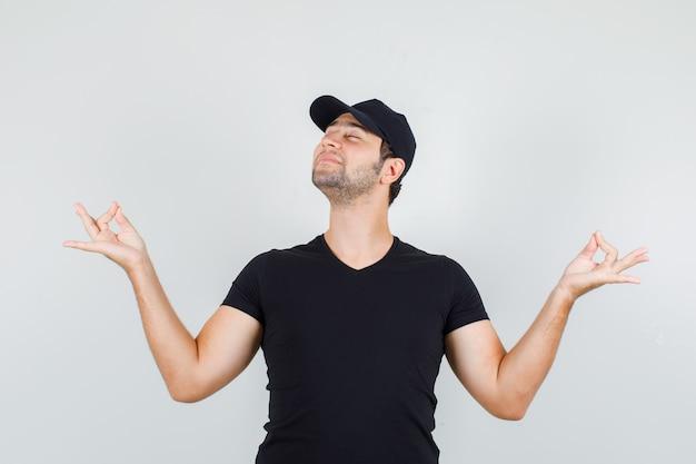 Człowiek Dostawy Robi Medytację Z Zamkniętymi Oczami W Czarnej Koszulce, Czapce I Wygląda Na Zrelaksowanego. Darmowe Zdjęcia