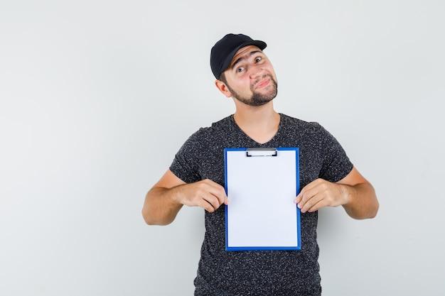 Człowiek Dostawy, Trzymając Schowek W T-shirt I Czapkę I Patrząc Pozytywnie Darmowe Zdjęcia