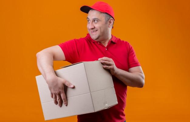 Człowiek Dostawy Ubrany W Czerwony Mundur I Czapkę, Trzymając Duży Karton, Patrząc Na Bok Uśmiechnięty Miejsce Stojące Darmowe Zdjęcia