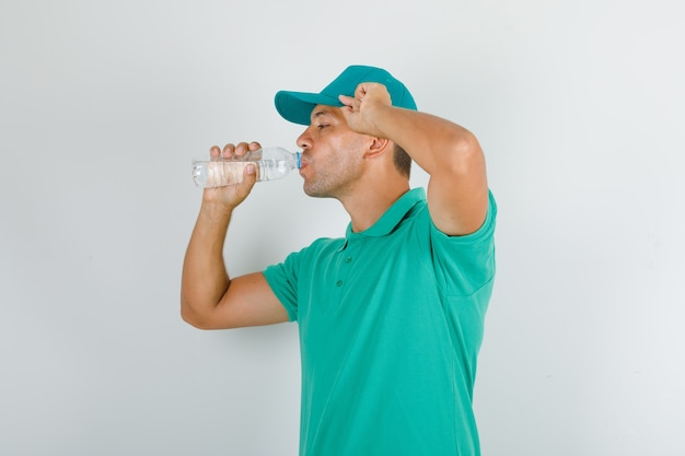 Człowiek Dostawy W Zielonej Koszulce I Czapce Wody Pitnej I Patrząc Spragniony Darmowe Zdjęcia