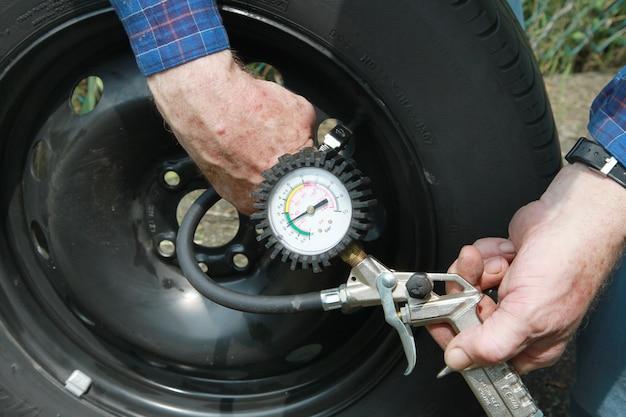Człowiek pomiaru ciśnienia w oponach Premium Zdjęcia