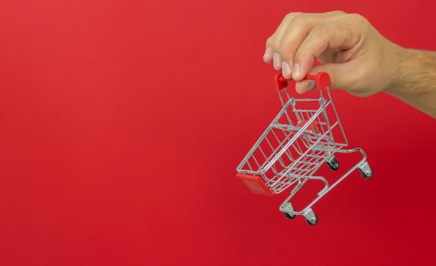 Człowiek Posiadający Mały Wózek Wózek Na Zakupy Na Czerwono. Zakupy Online I Koncepcja Szybkiej Dostawy Premium Zdjęcia