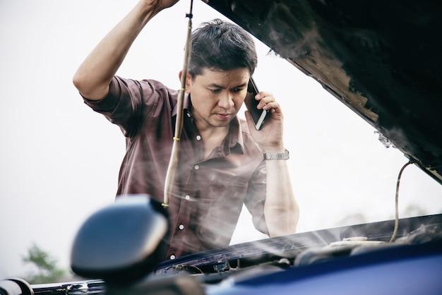 Człowiek próbuje naprawić problem silnika samochodowego na drodze lokalnej Darmowe Zdjęcia
