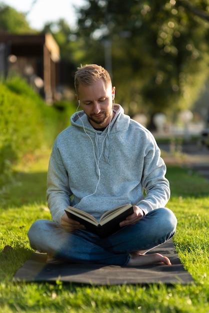 Człowiek Robi Pozycję Lotosu Podczas Czytania Książki Darmowe Zdjęcia