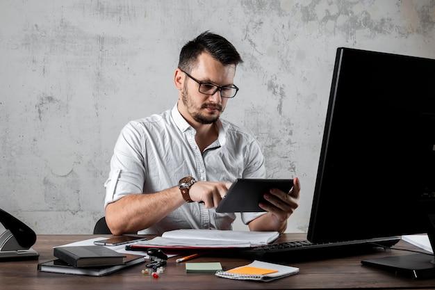 Człowiek Siedzi Przy Stole W Biurze, Grając W Telefonie. Pojęcie Pracy Biurowej, Lenistwo, Zmęczenie. Skopiuj Miejsce. Premium Zdjęcia