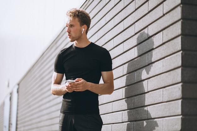 Człowiek sportowy jogging rano w mieście i przy użyciu telefonu Darmowe Zdjęcia