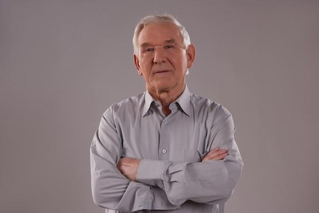 Człowiek stoi na szarym tle z skrzyżowanymi rękami Premium Zdjęcia