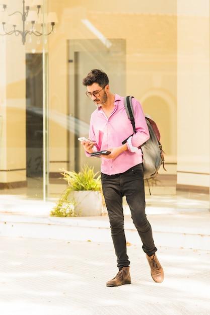 Człowiek Stojący Na Zewnątrz Z Plecakiem Za Pomocą Telefonu Komórkowego Darmowe Zdjęcia