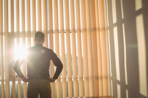 Człowiek Stojący Z Rękami Na Biodrze W Pobliżu Rolet Okiennych Darmowe Zdjęcia