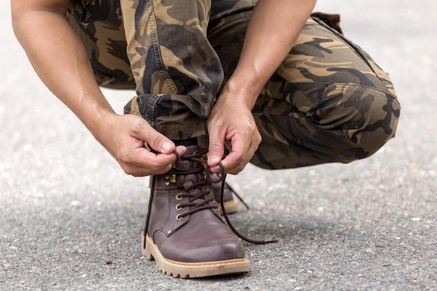 Człowiek ubrany w spodnie cargo i wiązanie sznurówek na buty skórzane buty Premium Zdjęcia