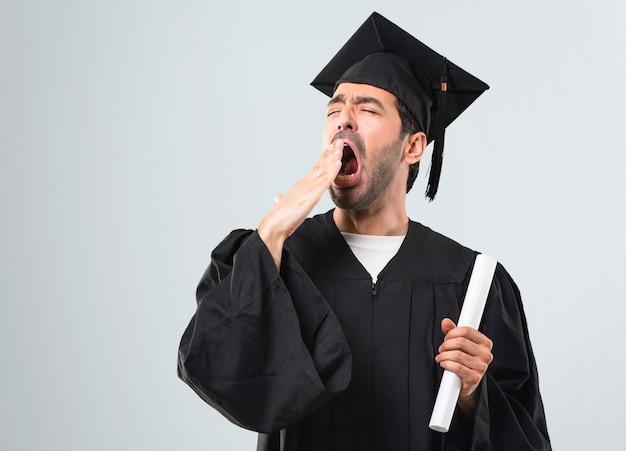 Człowiek W Dniu Jego Ukończenia Uniwersytet Ziewanie I Obejmujące Szeroko Otwarte Usta Ręką Premium Zdjęcia