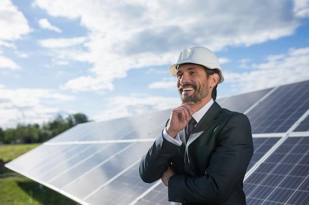 Człowiek W Garniturze Szczęśliwie Smailing, Panele Słoneczne Na Zapleczu. Premium Zdjęcia