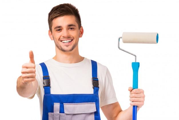 Człowiek w ubraniach roboczych maluje ściany w pokoju. Premium Zdjęcia