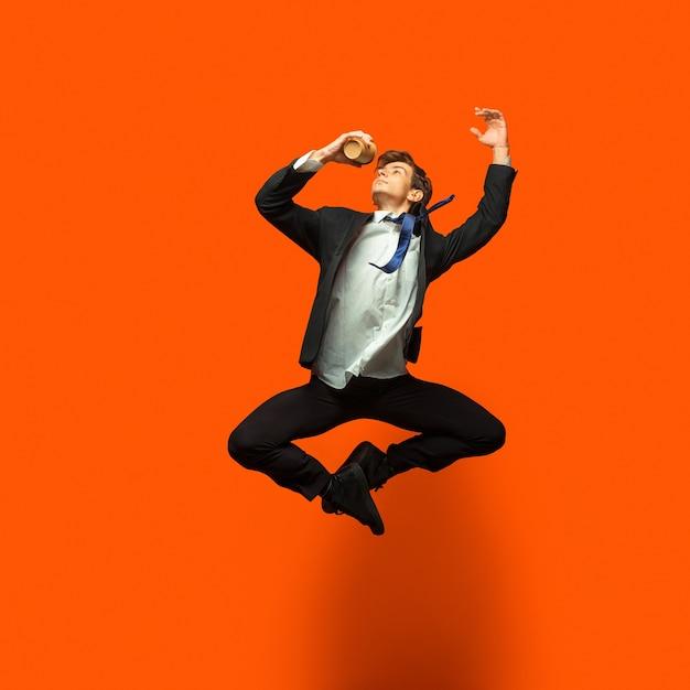 Człowiek W Ubranie W Stylu Casual Office Skoki I Taniec Na Białym Tle Na Jasny Pomarańczowy Darmowe Zdjęcia