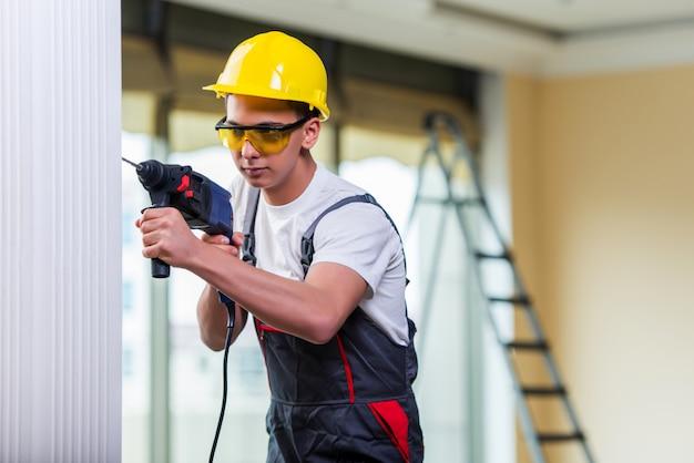 Człowiek, wiercenie ściany za pomocą perforatora wiertarki Premium Zdjęcia