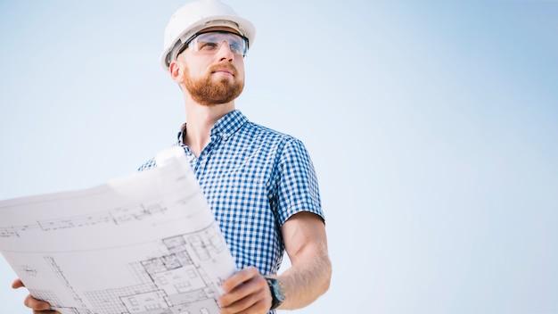 Człowiek Z Blueprint Patrząc Od Hotelu Premium Zdjęcia