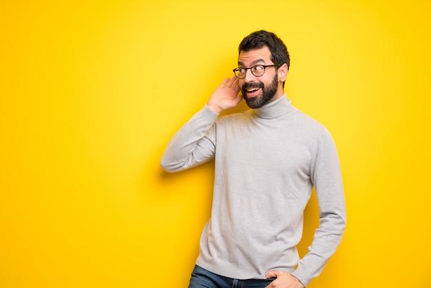 Człowiek Z Brodą I Golfem Słuchając Czegoś, Kładąc Rękę Na Uchu Premium Zdjęcia