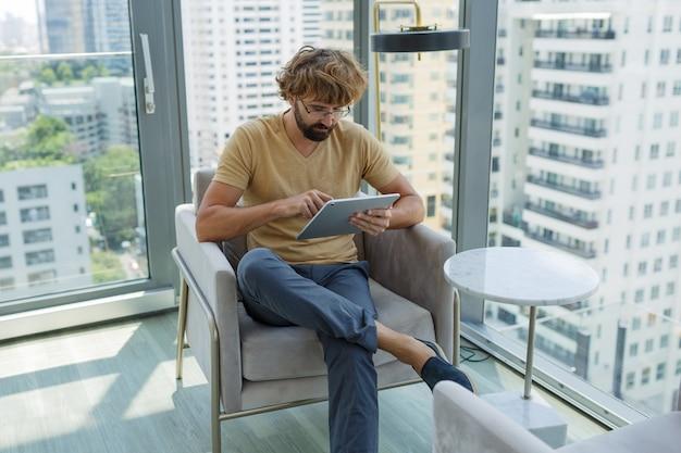 Człowiek Z Tabletem, Siedząc Na Kanapie W Nowoczesnym Biurze. Darmowe Zdjęcia