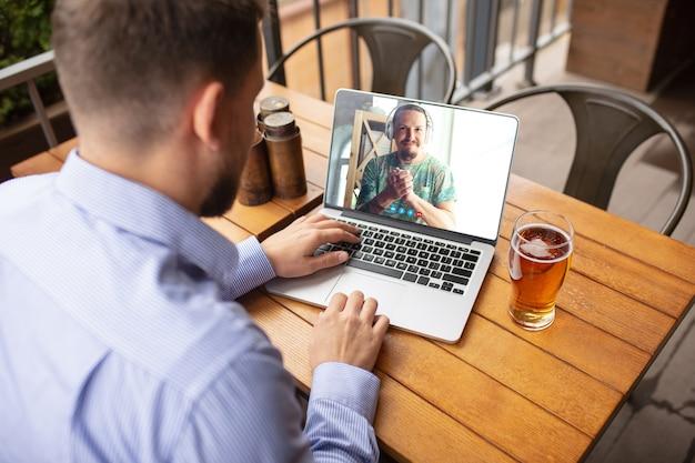 Człowiek Za Pomocą Laptopa Do Wideorozmowy Podczas Picia Piwa Darmowe Zdjęcia
