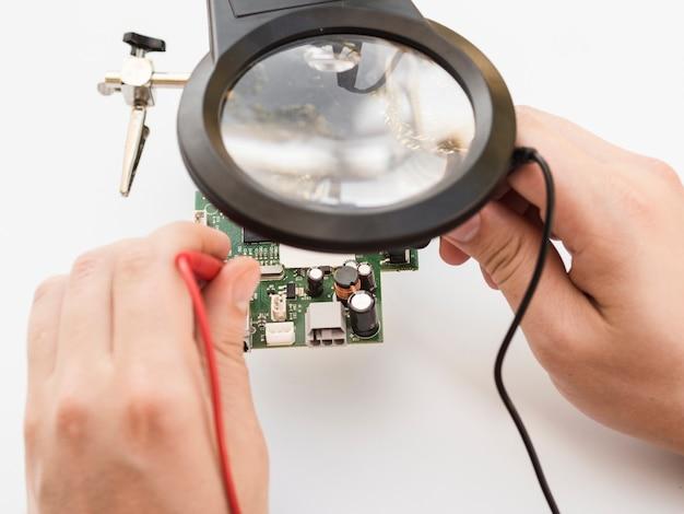 Człowiek Za Pomocą Multimetru, Aby Sprawdzić Tablicę Darmowe Zdjęcia