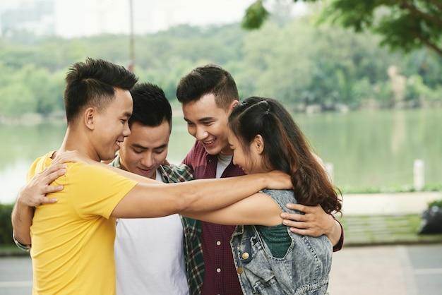 Czterech nastolatków przytulanie na zewnątrz nad rzeką Darmowe Zdjęcia