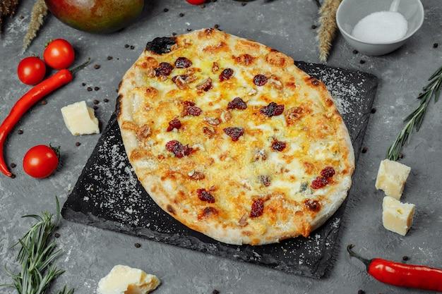 Cztery Gorące Sery Pyszne Rustykalna Amerykańska Pizza Z Grubą Skórką Na Czarnym Stole. Premium Zdjęcia