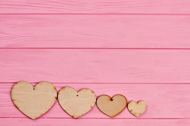 Cztery Serca Sklejki Na Kolorowym Tle. Wiersz Drewnianych Serc Na Różowym Tle Drewnianych Z Miejsca Na Kopię. Walentynki Kartkę Z życzeniami. Premium Zdjęcia