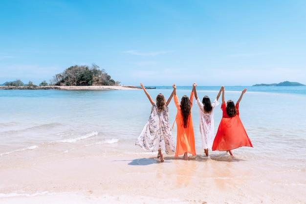 Cztery Urocze Dziewczyny W Kolorowych Tunikach Stoją Na Plaży, Trzymając Się Za Ręce, Trzymając Się Nawzajem. Letnie Wakacje Na Tropikalnej Plaży. Premium Zdjęcia