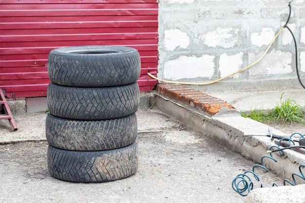 Cztery Używane Opony Samochodowe Ułożone Jedna Na Drugiej W Pobliżu Sklepu Z Oponami. Wymiana Koła W Serwisie Opon Premium Zdjęcia