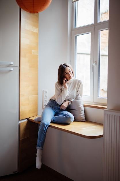 Czuła Młoda Kobieta Siedzi Na Szerokim Windowhill W Niebieskich Dżinsach I Białej Koszulce Darmowe Zdjęcia