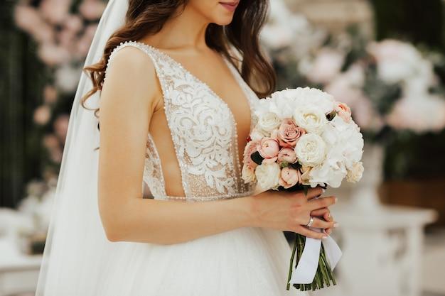 Czuła Panna Młoda Trzyma W Rękach Bukiet Z Białych I Różowych Róż. Premium Zdjęcia