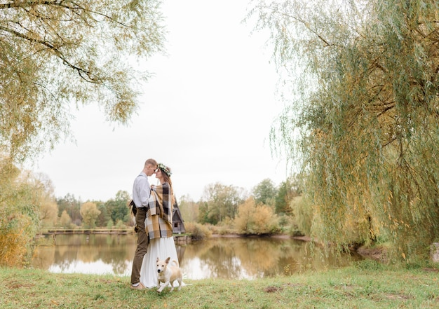 Czuła Para Zakochana W Jesiennym Parku Z Psem Stoi Prawie Całując Się Nad Jeziorem Darmowe Zdjęcia