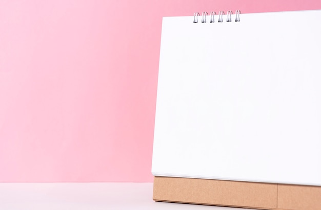 Czysty papier spirala kalendarz na makieta szablon reklamy i marki na różowym tle. Premium Zdjęcia
