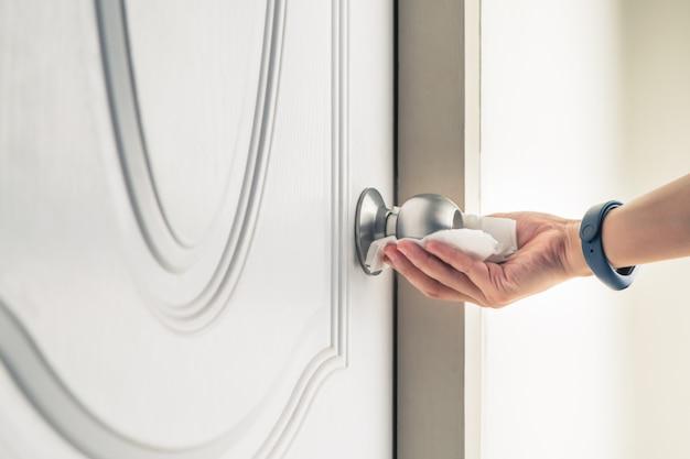 Czyszczenie Gałki Drzwi Za Pomocą Aerozolu Alkoholowego W Celu Zapobiegania Koronawirusowi Covid-19 Premium Zdjęcia