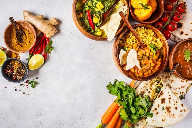 Dal, palak paneer, curry, ryż, chapati, chutney w drewnianych misach na białym stole. Premium Zdjęcia