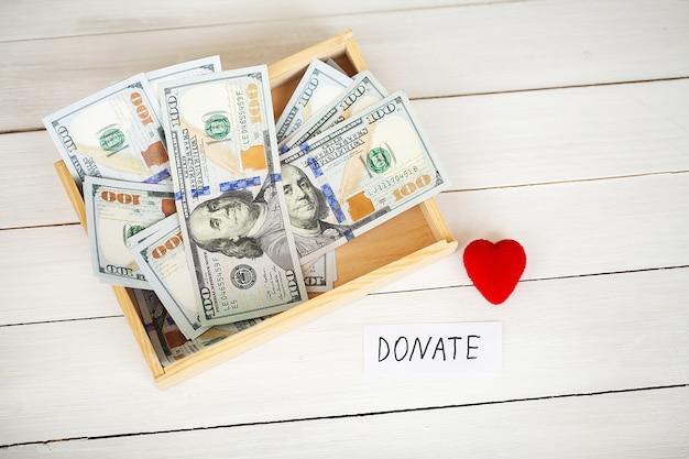Darowizny i cele charytatywne. darowizna pudełko darowizn i serce na białym. Premium Zdjęcia