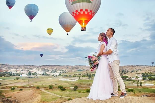 Data Zakochanej Pary O Zachodzie Słońca Przed Balonami W Kapadocji Premium Zdjęcia