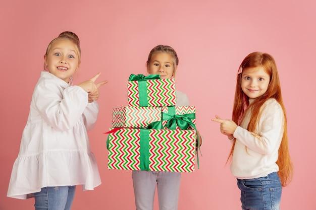 Dawanie I Otrzymywanie Prezentów Na święta Bożego Narodzenia. Grupa Szczęśliwych Uśmiechniętych Dzieci Zabawy, świętuje Na Białym Tle Na Różowym Tle Studio. Spotkanie Noworoczne 2021, Dzieciństwo, Szczęście, Emocje. Darmowe Zdjęcia