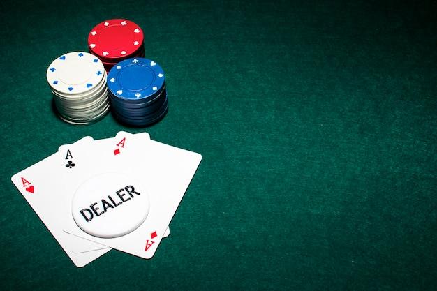 Dealer Chip Na Karcie Asów I Stos żetonów Na Zielonym Tle Pokera Premium Zdjęcia