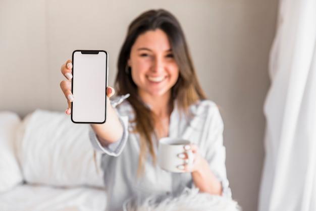 Defocused Młoda Kobieta Pokazuje Białego Pustego Ekranu Telefon Komórkowego Darmowe Zdjęcia