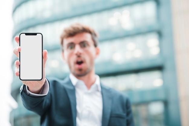 Defocussed Młody Biznesmen Pokazuje Telefon Komórkowego Darmowe Zdjęcia
