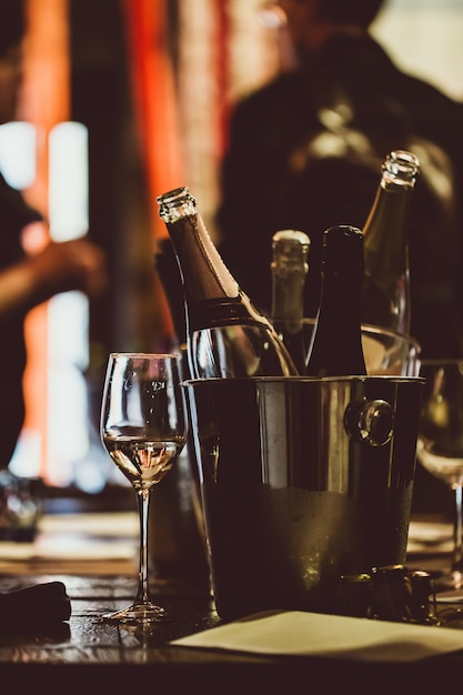 Degustacja Wina: Na Drewnianym Stole Znajduje Się Srebrne Wiadro Do Chłodzenia Wina Z Otwartymi Butelkami. Premium Zdjęcia